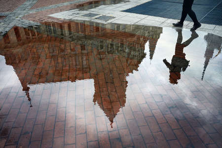 Woman reflection in puddle at Europe Square in Batumi