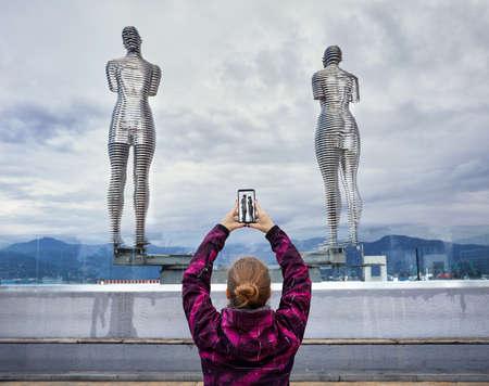 Tourist Woman tacking picture of statues Ali and Nino with smartphone in Batumi, Georgia