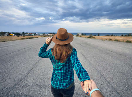 Happy couple in checked shirt holding by hands and walking on the wide asphalt road with lake and cloudy sky background Фото со стока