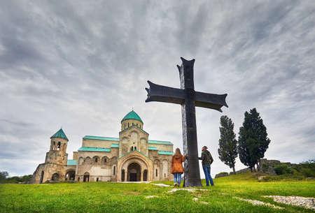 Tourist couple near big Cross in front of Bagrati church at overcast sky in Kutaisi, Georgia