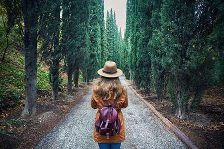 Vrouw die in bruine hoed met rugzak cipressteeg bekijken in botanische tuin van Tbilisi, Georgië Stockfoto
