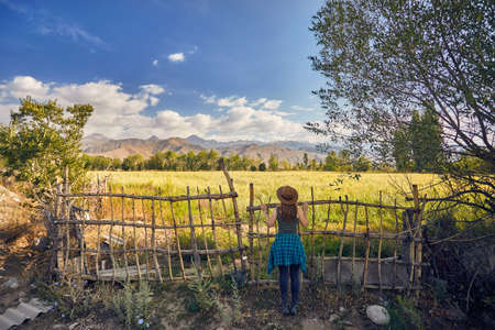 Woman in hat and green checked shirt near the fence gate looking at field in the farm at the morning Stock Photo