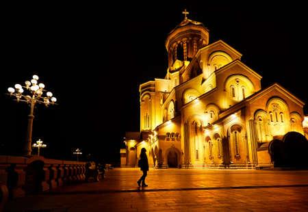 Woman silhouette near The Holy Trinity Cathedral or Tsminda Sameba Church at night in Tbilisi, Georgia