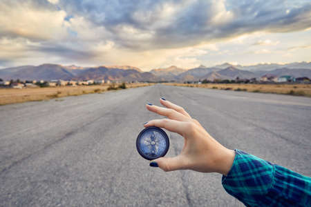 Woman hand in green shirt holding compass at sunrise sky background. Travel and adventure concept.