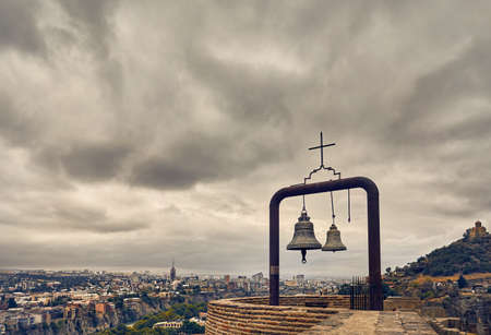 Old medieval castle Narikala with big bells on the wall at overcast cloudy sky in Tbilisi, Georgia Stock Photo
