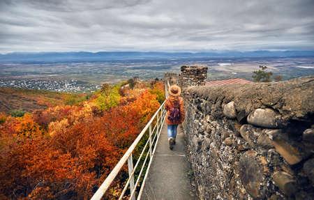 シグナギ、ジョージア州の秋にアラザニ渓谷を眺めながら古代都市の壁を歩いている茶色の帽子とバックパックの観光女性 写真素材
