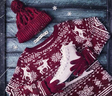Red sweater holding white skates on wooden blue background at winter holidays Stock Photo