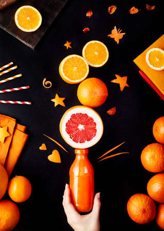 Fresh detox juice from oranges, grapefruit and lemon on black background flay lay