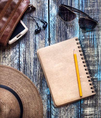 木製のテーブルの近くの旅行帽子、サングラス、バッグ スマート フォンでテキストの空スペースとビンテージの論文誌