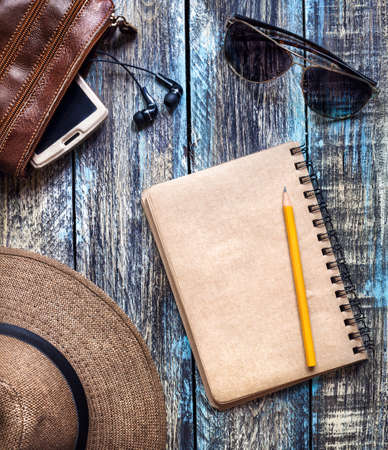 Vintage Paper journal with empty space for your text near travel hat, sunglasses and bag with smartphone on wooden table