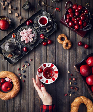 Woman touching red tea near Turkish delights rahat lokum, simits and fruits on wooden table