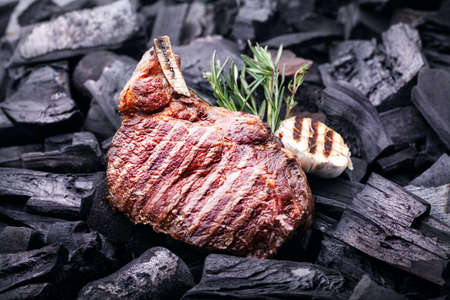 Grilled meat steak with garlic and rosemary on black coals at barbeque cookout