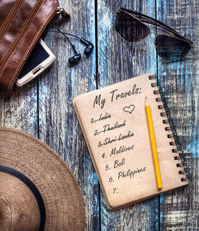 Vintage Paper Diary with travel dream list of South East Asian countries on wooden rustic table