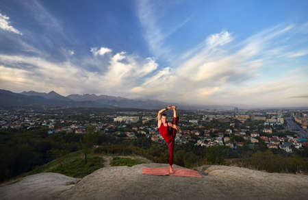 Fit man in red costume doing yoga balance asana in the park with city and mountain on background in Almaty, Kazakhstan