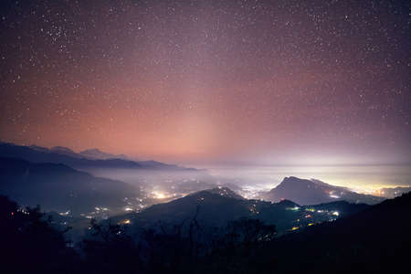 Lights of Pokhara city and villages at night starry sky at mountain range of Annapurna, Nepal Stock Photo