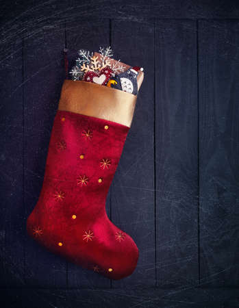 Red stocking with presents and toys on wooden background on Christmas