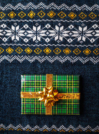 Green wrapped present with golden bow on man sweater at Christmas time