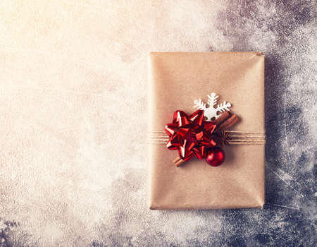 Wrapped present with red bow on textured winter background Stock Photo
