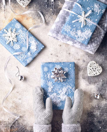 Girl in grey mittens holding blue wrapped present on Christmas Stock Photo