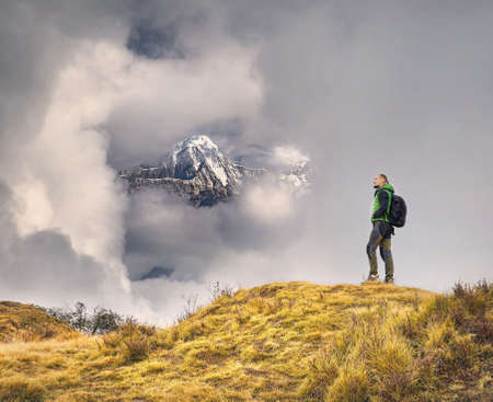 Tourist with backpack enjoying the view of snowy Himalayan Mountain at cloudy sky in Nepal