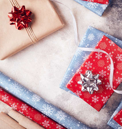 Wrapping presents with red and blue papers on white textured background on Christmas Stock Photo