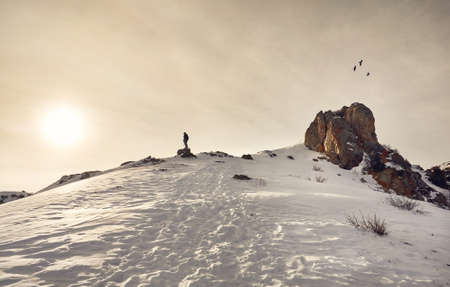 Hiker standing on the rock with trekking poles enjoying the view of snowy mountains at dramatic sunrise sky.