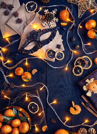 Mask, oranges and glowing lights on black wooden background at Christmas party Stock Photo