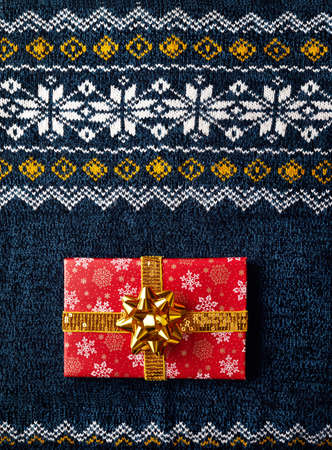 Red wrapped present with golden bow on man sweater at Christmas time