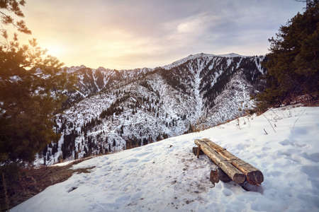 Wooden bench and panoramic view of high mountain range of Zaili Alatay and at sunrise from Kok Zhaylau trail in Almaty, Kazakhstan