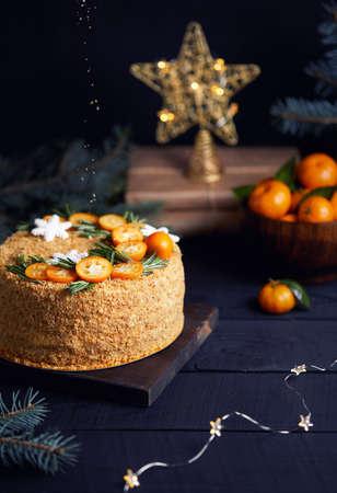 Christmas Honey cake with rosemary and oranges on black background.