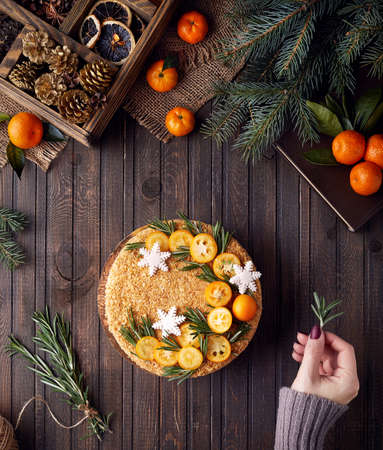 Woman decorates Christmas Honey cake with rosemary and oranges on brown wooden background. Stock Photo