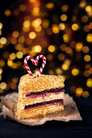 Piece of honey cake with blackberry and stripped candy sticks on the top in heart shape at Christmas time Stock Photo