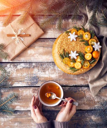 Christmas Honey cake on the table. Woman holding tea with berry near decorated present at breakfast.