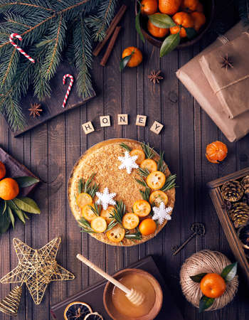 Christmas Honey cake with rosemary and oranges on brown wooden background.