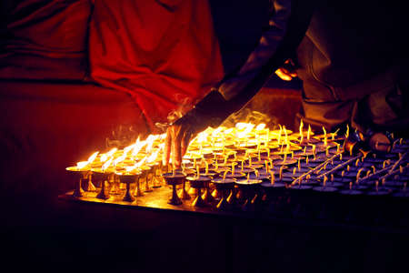 Monk fire the oil lamps of peace in the Buddhist Temple in Kathmandu Stock Photo