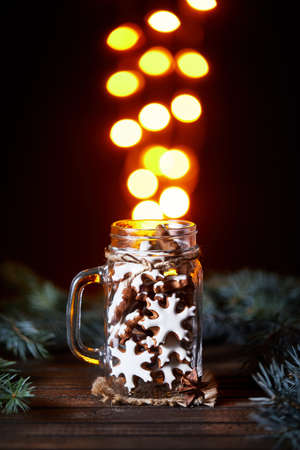 Gingerbread stars in the glass jar with golden bokeh lights at black background