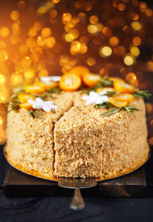 Christmas Honey cake with rosemary and oranges on black table and golden bokeh background.