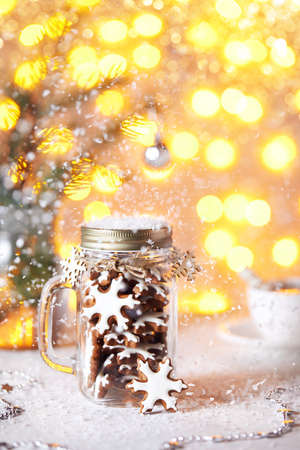 Gingerbread stars in the glass jar on white table at golden bokeh background with snow around. Stock Photo