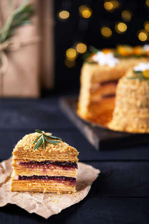 Piece of Christmas Honey cake with rosemary and oranges on black background.