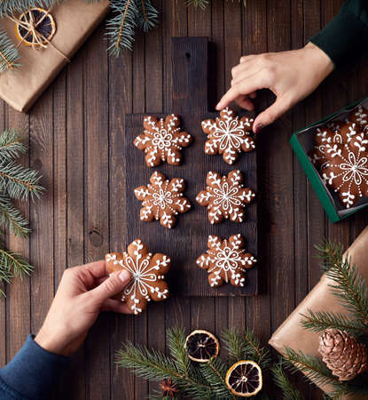 Man and woman holding Christmas gingerbread stars on rustic wooden background