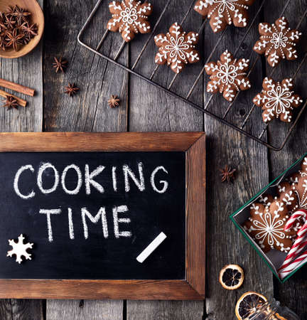 Cooking time for Christmas gingerbread stars on rustic wooden background