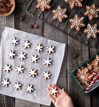 Woman cooking Christmas gingerbread stars on rustic wooden background