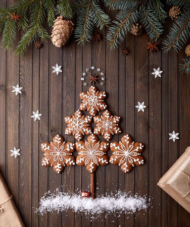 Christmas tree from gingerbread stars with snow around on rustic brown background