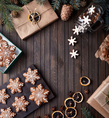 Christmas gingerbread stars and dry oranges on rustic wooden background