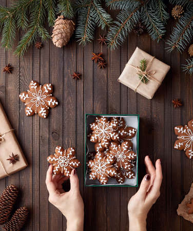 Woman holding gingerbread stars in the box on rustic brown background Stock Photo