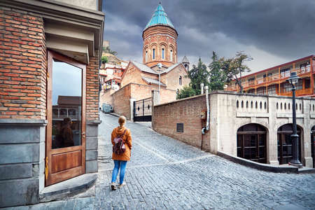 Tourist woman in brown jacket walking down the Old streets near church in central Tbilisi, Georgia