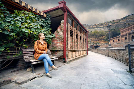 Tourist woman in brown jacket sitting on the bench near Public Sulfuric bath district in central Tbilisi, Georgia