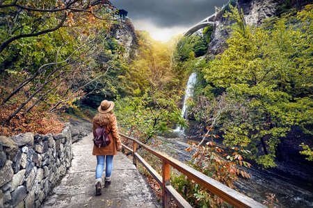 Tourist Woman in Hat going to waterfall in Botanical Garden with autumn trees at overcast cloudy sky in Tbilisi, Georgia Stock Photo