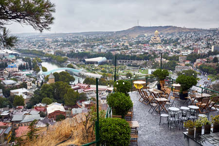 Empty cafe at Narikala Fortress with panoramic view Tbilisi at overcast sky, Georgia