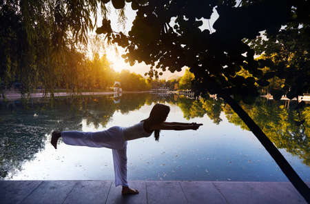 Beautiful Asian girl in white costume doing yoga near the lake in the park at sunrise Stock Photo